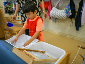 Kid learning to wash at our montessori school