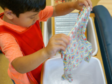 kid learning to wash clothes